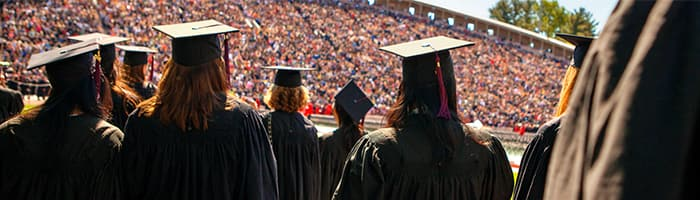 Students standing in full stadium on graduation day